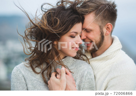 Close-up portrait of couple with wind in hair, hugging and happy together 72006866