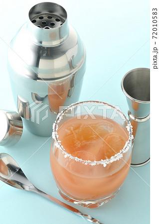 グラスの縁に塩が付いているピンクソルティドッグとカクテルシェーカーとメジャーカップ 72010583