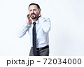 A man in a shirt stands and holds on to sore neck. 72034000