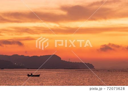 広島県 夜明けの瀬戸内で漁をする小舟 72073628