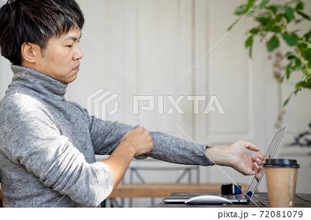 薄型のおしゃれなノートパソコンで気分転換をして仕事をする男性のイメージ 72081079