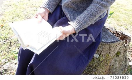 切り株に座って読書してリラックスする日本人女性 72083639