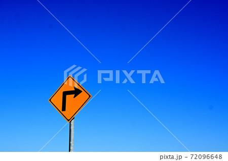 青い空に映える矢印の描かれた黄色の標識 72096648