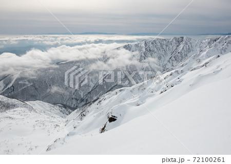 長野の白馬にある冬季唐松岳の八方尾根ルート上の八方ケルン付近の雲海と遠見尾根 72100261