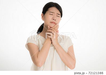 のどを抑えて病状に悩む日本人の若い女性 72121386