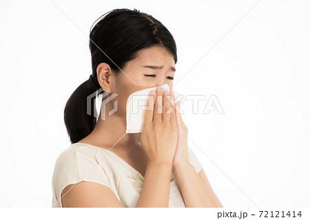ティッシュで鼻をかみながら病状に悩む女性 72121414