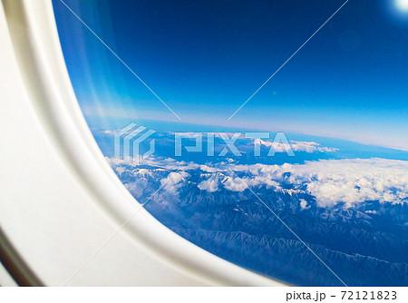 飛行機の窓から見える透き通る青空の中の富士山 72121823