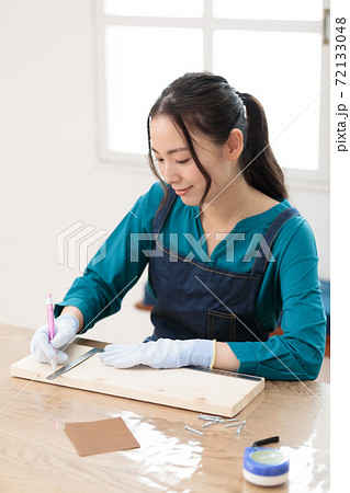 木材カットのために墨線をひくDIY女子 72133048