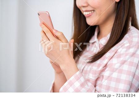 スマホを操作するパジャマの若い女性(パーツ) 72138334