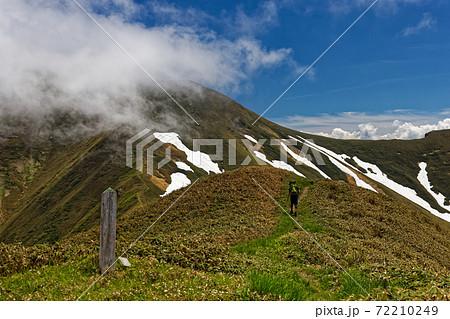 谷川連峰・小障子の頭付近の縦走路を行く登山者と雲湧くオジカ沢の頭 72210249