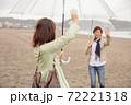 海辺の砂浜で手を振るカップル(お別れ) 72221318