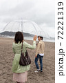 海辺の砂浜で手を振るカップル(お別れ) 72221319