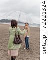 海辺の砂浜で手を振るカップル(お別れ) 72221324