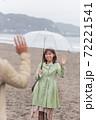 雨の海辺の砂浜で笑顔で挨拶するカップル(デート待合せ) 72221541