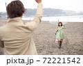 雨の海辺の砂浜で笑顔で挨拶するカップル(デート待合せ) 72221542