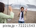 雨の海辺の砂浜で笑顔で挨拶するカップル(デート待合せ) 72221543