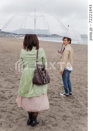 雨の降る海辺の砂浜で別れるカップル 72221643
