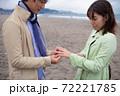 海辺の砂浜で指輪を着けるカップル 72221785
