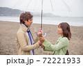 雨降る海辺の砂浜で女性から男性へ花束渡して告白 72221933