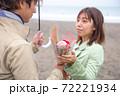 雨降る海辺の砂浜で女性から男性へ花束渡して告白 72221934