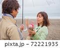 雨降る海辺の砂浜で女性から男性へ花束渡して告白 72221935