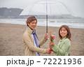 雨降る海辺の砂浜で女性から男性へ花束渡して告白 72221936