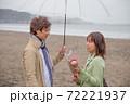 雨降る海辺の砂浜で女性から男性へ花束渡して告白 72221937