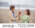 雨降る海辺の砂浜で女性から男性へ花束渡して告白 72221938