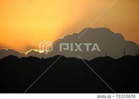 5月下旬の初夏の分厚い雲に沈んでゆく夕日 72223676