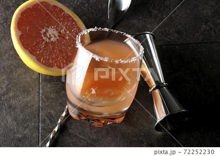 グラスの縁に塩が付いているソルティドッグとカットされたグレープフルーツとスプーンとメジャーカップ 72252230