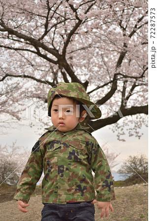 春の桜をバックに迷彩のの軍服でキメる男の子 72287573