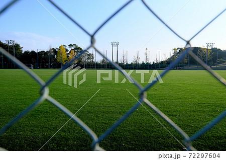 フェンス越しに見た綺麗な芝生のグランド 72297604