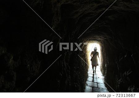 トンネルから光明に向かって歩みを進める女性 72313667