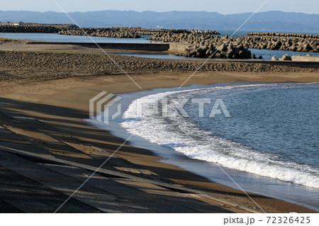 砂浜のビーチに打ち寄せる波と消波ブロック 72326425