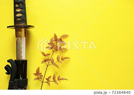 黄色い紙の背景の左に置いた抜きかけの日本刀と赤い葉の木の枝。右側半分がコピースペース。 72364640