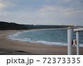 白波が打ち寄せる静かな砂浜 72373335