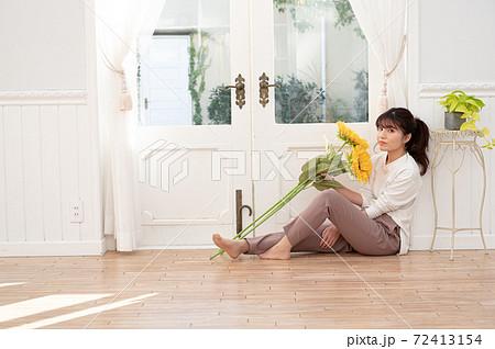 ひまわりの束をもって床に座る若い女性 72413154