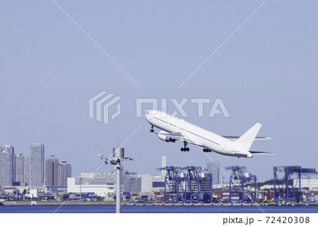 青空を背景に羽田空港を離陸する飛行機と東京湾に面した都心ビル群とクレーン 72420308
