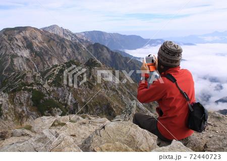 唐松岳から秋の後立山連峰(不帰キレット、白馬三山方面)を撮影する男性 72440723