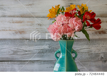 青い花瓶に活けたアルストロメリアカーネーションの花束 72464440