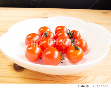 白い皿の上で光る赤いプチトマトたち 72476682