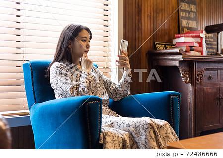 アンティークな椅子に座りスマホを使う女性  72486666