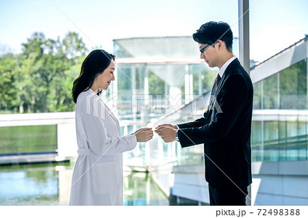 病院で名刺交換する白衣の女医とスーツの男性MRの医療イメージ 72498388