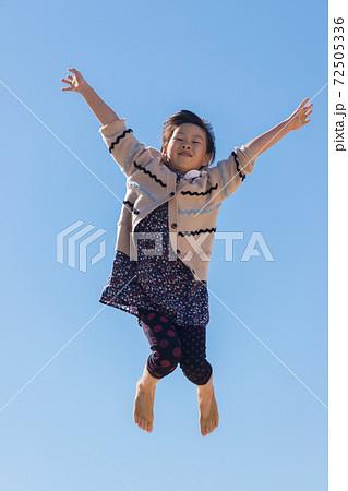ビーチで跳んで遊んでいる可愛い子供と青空の風景 72505336