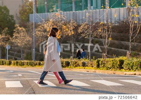 秋の夕方の町並みの風景と横断歩道を歩く親子の姿 72506642