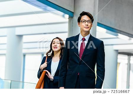会社の廊下を颯爽と歩くスーツを着た男女のビジネスチーム 72516667