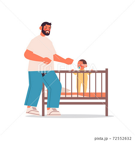 young father playing with little son in crib fatherhood concept dad spending time with his kid full length 72552632