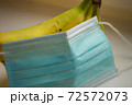 Bunch of bananas and medical mask on white table closeup 72572073
