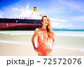Happy woman in orange swimsuit on beach against cargo ship 72572076