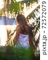 Woman in lacy dress sitting on rock against palm leaves 72572079